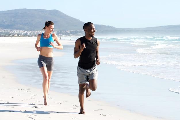 Casal ativo saudável correndo pela água na praia