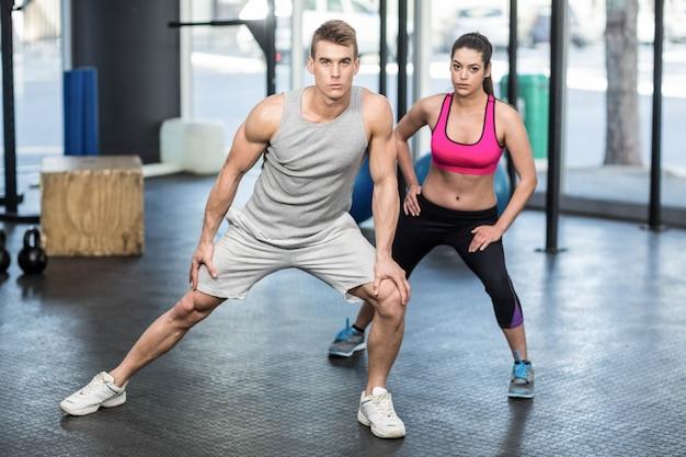Casal atlético alongamento no ginásio