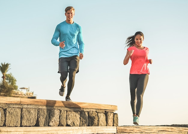 Casal atlético de amigos correndo ao ar livre no parque da cidade
