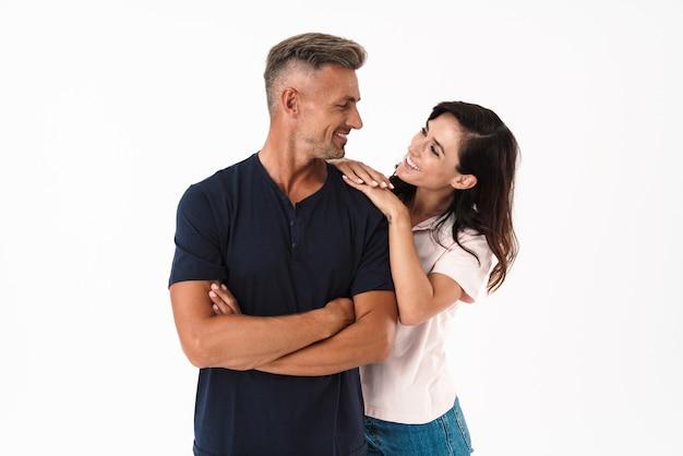 Casal atraente alegre apaixonado, vestindo roupa casual, em pé, isolado na parede branca, se abraçando