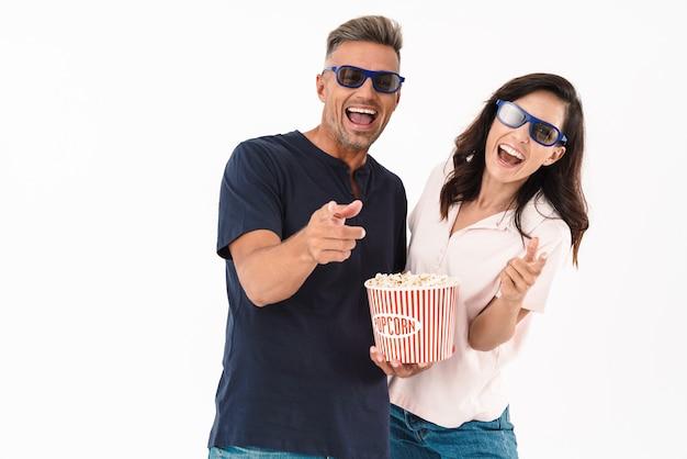 Casal atraente alegre, vestindo roupa casual, em pé, isolado na parede branca, assistindo a um filme com pipoca e óculos 3d