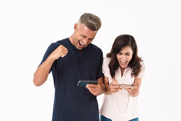Casal atraente alegre, vestindo roupa casual, em pé, isolado na parede branca, jogando em telefones celulares