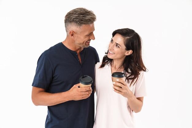 Casal atraente alegre, vestindo roupa casual, em pé, isolado na parede branca, segurando xícaras de café para viagem, olhando um para o outro