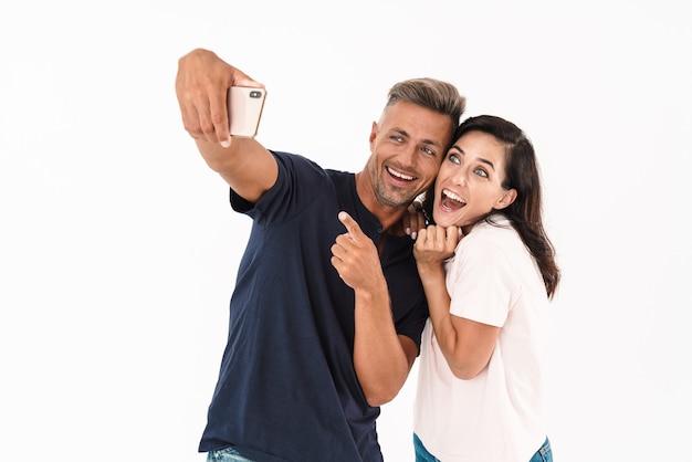 Casal atraente alegre, vestindo roupa casual, em pé, isolado na parede branca, tirando uma selfie, gritando