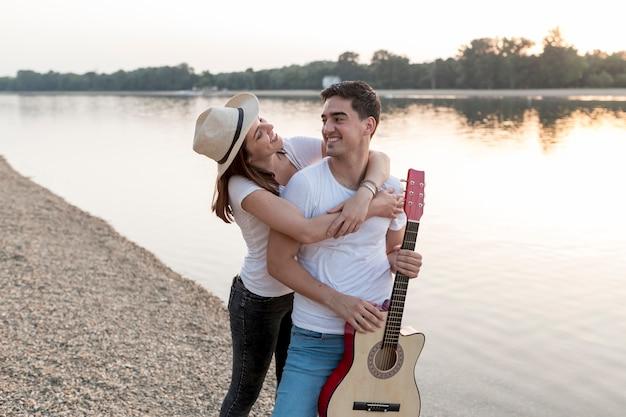 Casal atraente andando à beira do lago com guitarra