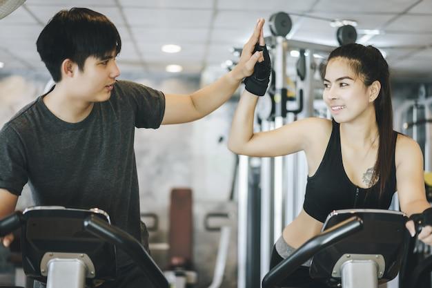 Casal atraente andando na bicicleta girando e dando um ao outro mais cinco no ginásio. trabalhando juntos