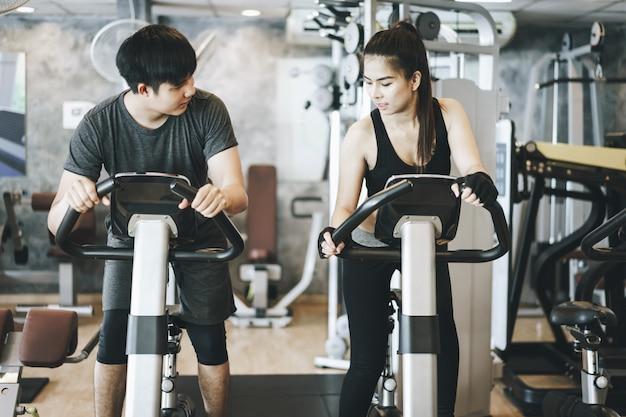 Casal atraente, andar de bicicleta na academia de giro. trabalhando juntos