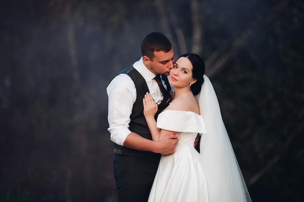 Casal atraente apaixonado posa para álbum de casamento, imagem isolada em fundo escuro