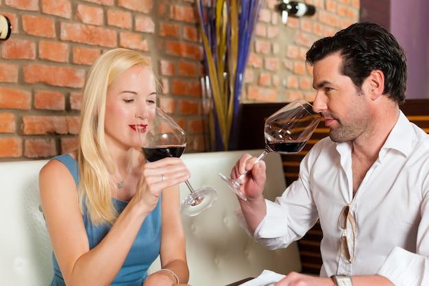 Casal atraente, bebendo vinho tinto no restaurante ou bar