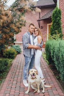 Casal atraente com cachorro labrador no parque
