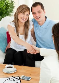 Casal atraente, concluindo um contrato de carro com um traficante na sala de estar