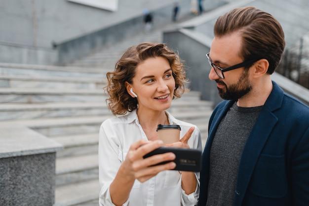 Casal atraente de homem e mulher conversando no centro urbano da cidade, segurando o telefone e olhando