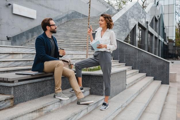 Casal atraente de homem e mulher sentados em escadas em uma cidade urbana