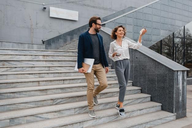 Casal atraente de homem e mulher subindo escadas no centro urbano da cidade, segurando laptop, discutindo