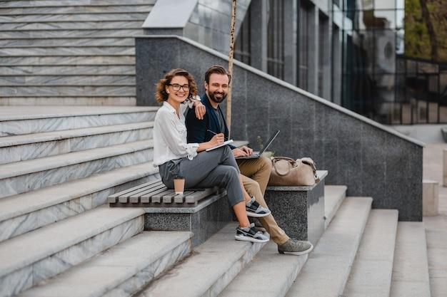 Casal atraente de um homem e uma mulher conversando sentados na escada no centro urbano da cidade