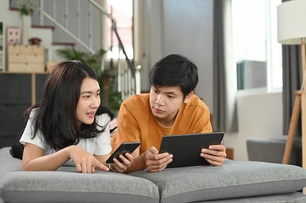 Casal atraente e casual está deitado no sofá enquanto navega na internet em casa