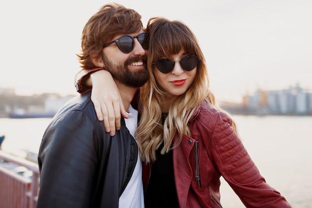 Casal atraente e elegante apaixonado posando ao ar livre, abraçando e caminhando no cais. cores suaves à noite. aparência elegante. óculos de sol da moda. homem e mulher constrangedores.