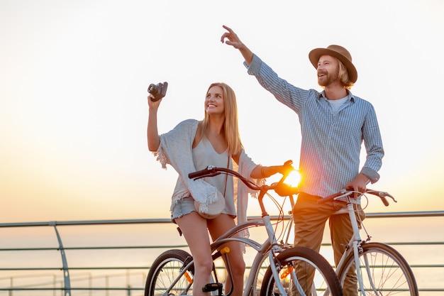 Casal atraente e feliz viajando no verão em bicicletas, homem e mulher com cabelo loiro boho hipster estilo moda se divertindo juntos, tirando fotos de passeios turísticos