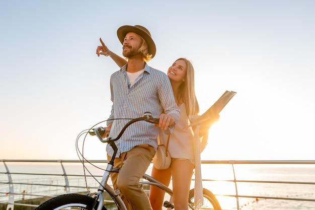 Casal atraente e feliz viajando no verão em bicicletas, homem e mulher no estilo boho hipster, se divertindo juntos, passeios turísticos, apontando o dedo