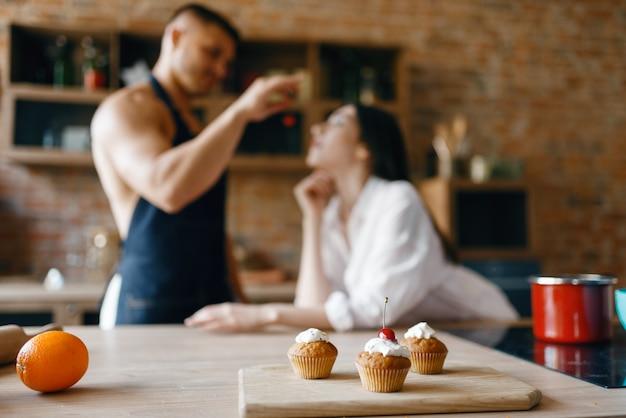 Casal atraente em cuecas cozinhando na cozinha