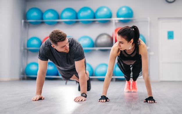 Casal atraente, empurrando no chão e olhando um ao outro no ginásio.
