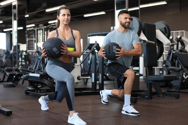 Casal atraente fazendo fitness com bola medcine no ginásio.
