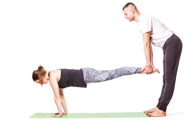 Casal atraente fazendo ioga juntos em fundo branco