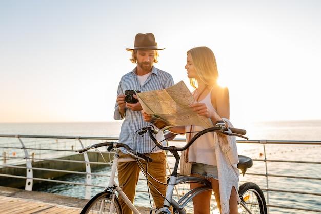 Casal atraente feliz viajando no verão em bicicletas, homem e mulher com cabelo loiro boho hipster estilo moda se divertindo juntos