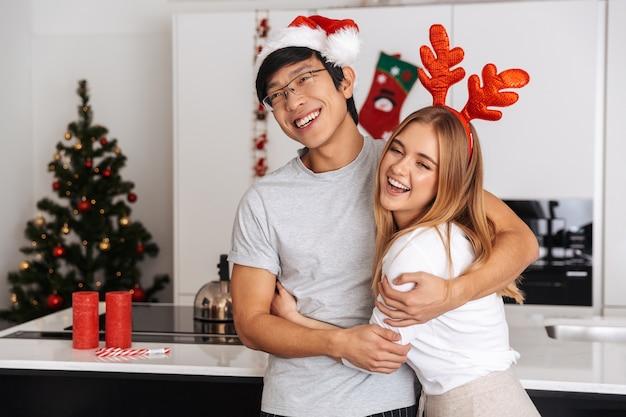 Casal atraente, homem e mulher vestindo roupas de natal, em pé na cozinha bem iluminada e se abraçando