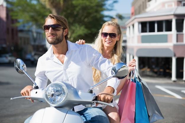 Casal atraente, montando uma scooter