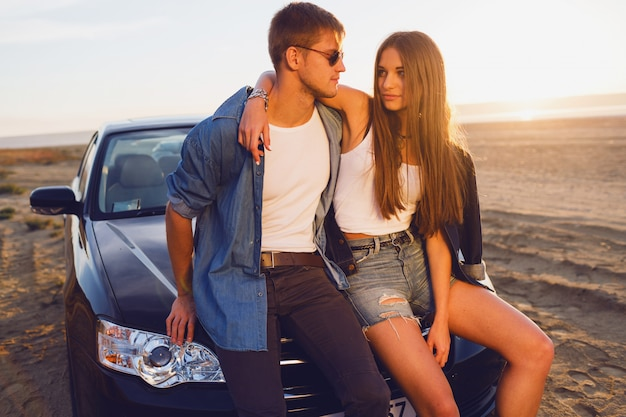 Casal atraente posando perto de carro na praia.