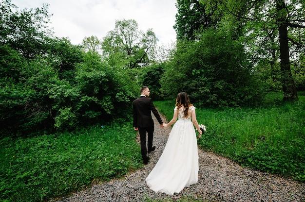 Casal atraente recém-casados está voltando por uma trilha em uma floresta verde. momento feliz e alegre.