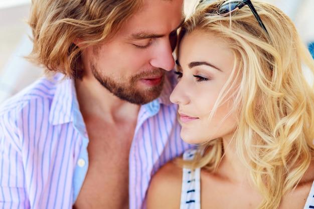 Casal atraente se abraçando na praia em um dia ensolarado