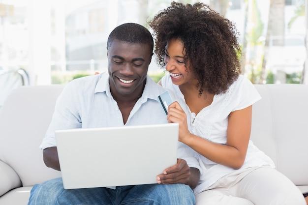 Casal atraente usando laptop juntos no sofá para comprar on-line