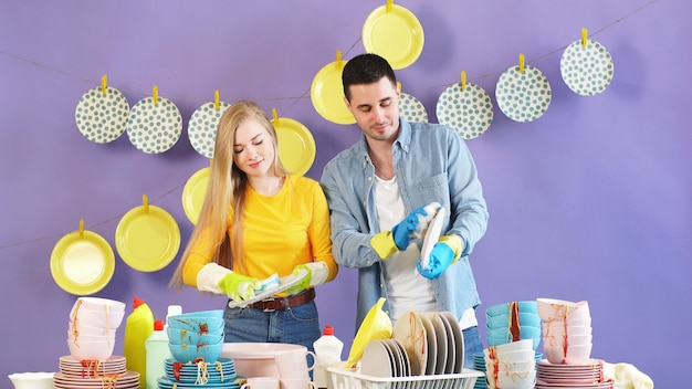 Casal atraente usando uma escova e esponja de lavar louça suja, pratos