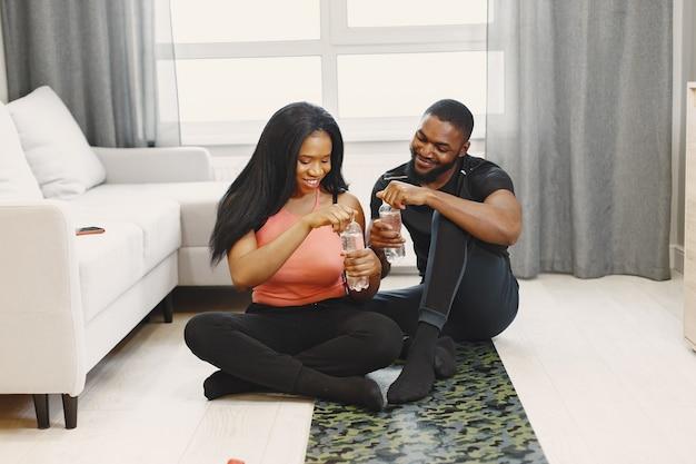 Casal bebendo água após o treino em casa
