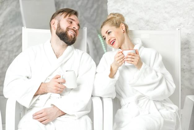 Casal bebendo água mineral sentado na sala de sal. aplicação de terapia de sal no spa