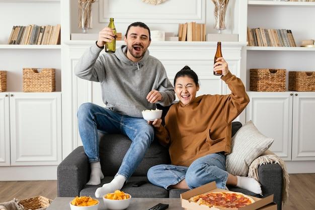 Casal bebendo cerveja e comendo lanches dentro de casa