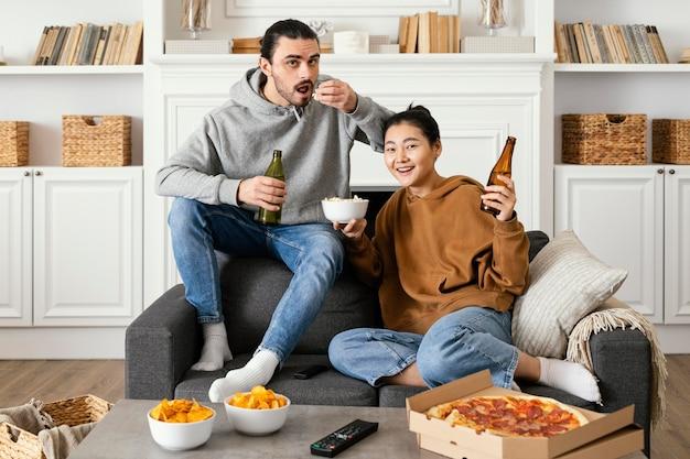 Casal bebendo cerveja e comendo salgadinhos