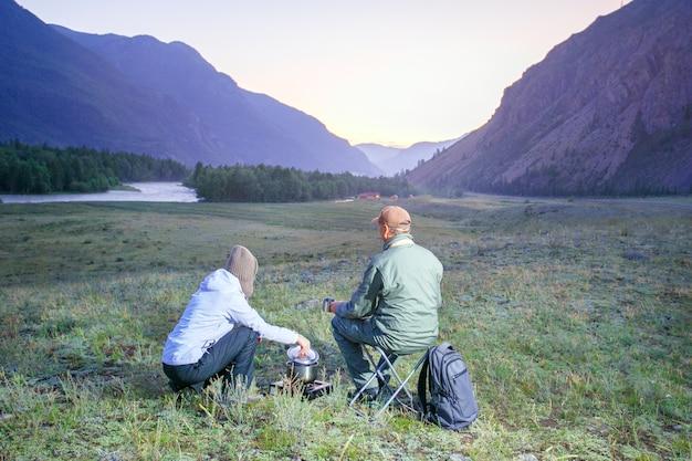Casal bebendo chá nas montanhas. viajante, amando o casal bebendo chá nas montanhas