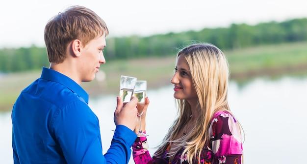 Casal bebendo champanhe ao ar livre, aproveitando as férias de verão