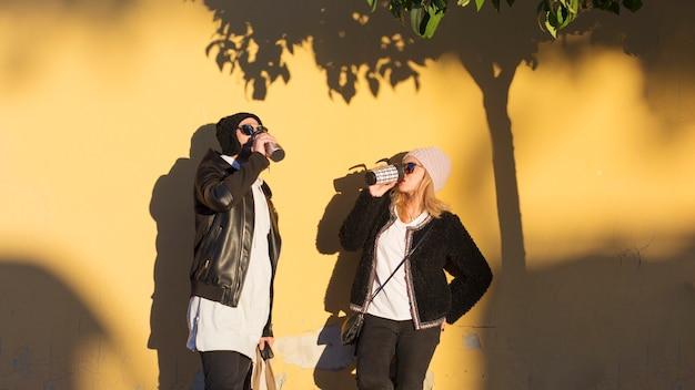 Casal bebendo de thermos perto da parede