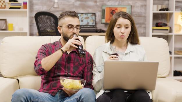 Casal bebendo refrigerante e comendo batatinhas enquanto navega no laptop. casal relaxando no sofá.