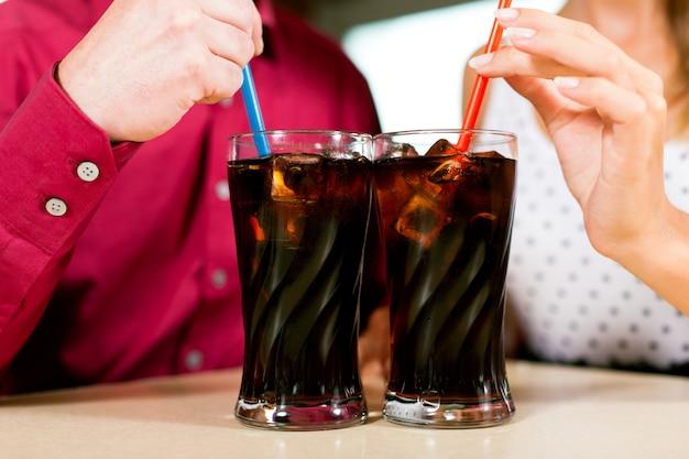 Casal bebendo refrigerante em um bar
