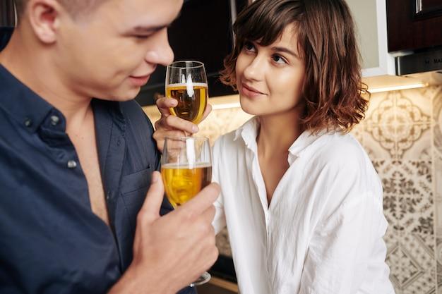Casal bebendo vinho branco na cozinha