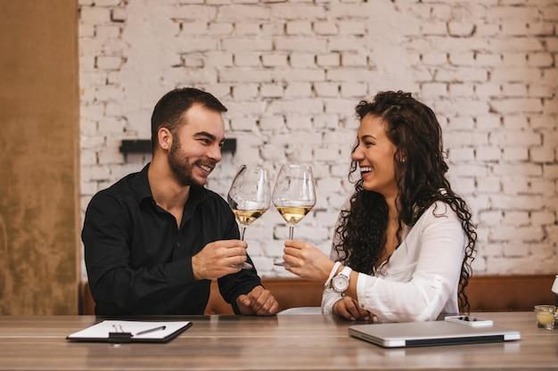 Casal bebendo vinho e comemorando após grande trabalho feito.