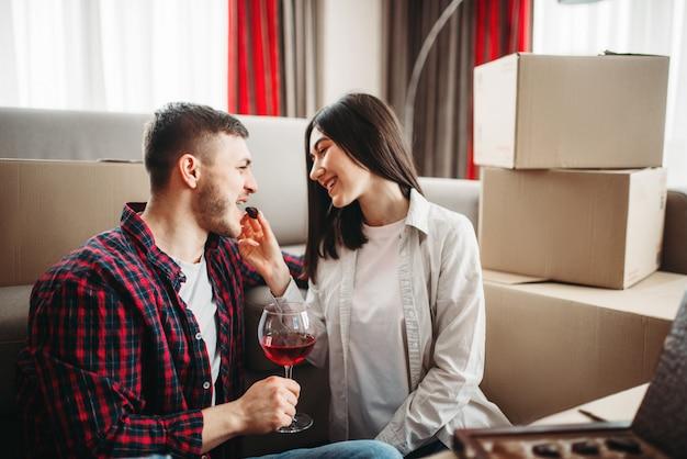 Casal bebendo vinho, mudando-se para a celebração da nova casa