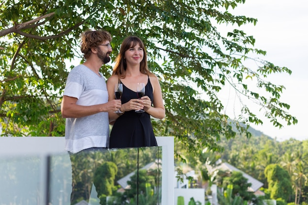 Casal bebendo vinho na varanda com vista para palmeiras tópicas.