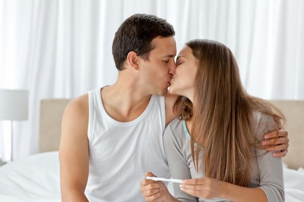 Casal beijando depois de analisar o resultado de uma prova de gravidez