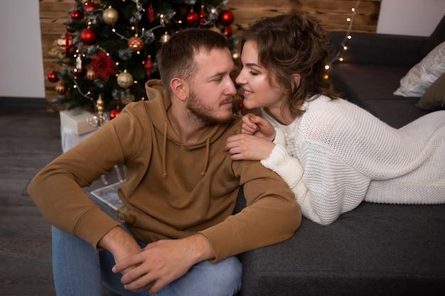 Casal beijando e comemorando o natal perto da árvore de natal